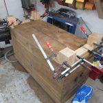 Mit zusätzlichen Klötzen stabilisiert er die Füße der alten Holztruhe.