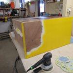 Gelbe Kommode wird beim Tischler im LK Harburg abgeschliffen